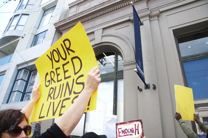 Manifestantes frente a la oficina de un propietario, exigen frenar desalojos en la Misión en abril de 2014. A group rallies outside of a property owners' office to protest evictions in the Mission in April 2014. Photo Shane Menez
