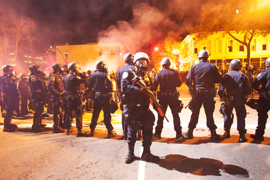 Police officers clad in full riot gear confront about 500 protesters on Broadway Street in Oakland on Nov. 24. Photo Santiago Mejia