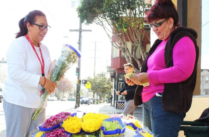 Dalia Gutierrez (at right) sells flowers on 24th Street. Photo Edgar Pacheco