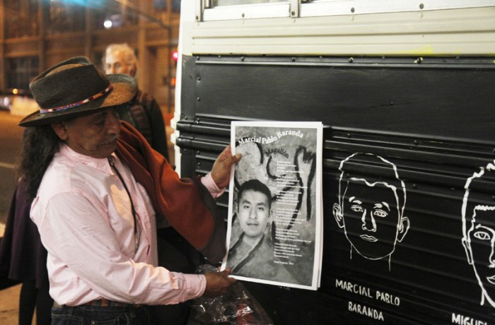 El artista y poeta Jorge Argueta sostiene su pieza de arte y poesía junto a un cuadro de Marcial Pablo Baranda, uno de los estudiantes mexicanos desaparecidos, en el autobús Gonzalo Guerrero El Grillo.
