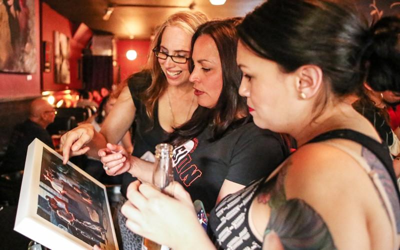 Karen Marino (izq), Raeann Biagini y Jessica Contreras ven a sus amigos en una foto antigua en Zoe's Bar & Restaurant para celebrar el cumpleaños 51 de Sandra Cuadra el 15 de febrero en San Francisco. Cuadra, líder de la comunidad e ícono de la Misión, murió de cáncer el 29 de octubre, 2013. Foto Joel Angel Juárez