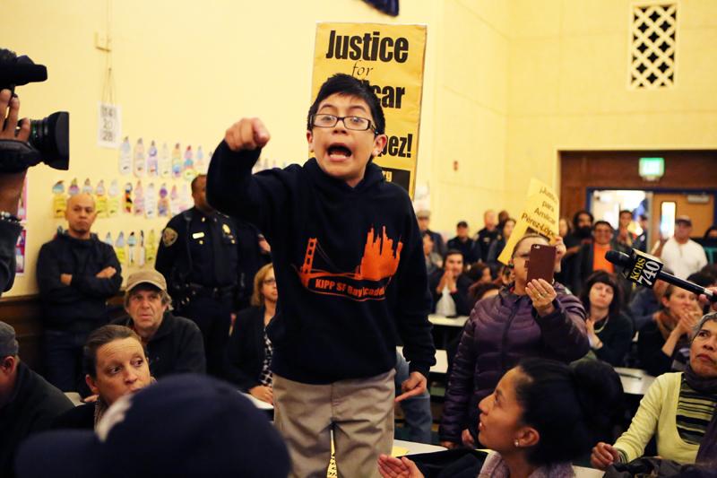 Un niño, cuya madre no quiso decir su nombre, se dirige hacia los comisionados de la policía de San Francisco, durante una reunion llevada a  cabo en la escuela primaria César Chávez el 2 de marzo. La reunión trató sobre el tiroteo a manos de la policía que ocasionó la muerte del joven de 21 años, Amilcar Perez-Lopez, el pasado 26 de febrero. Foto Joel Angel Juárez