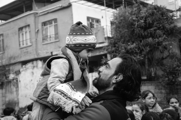 Mohammed Mustafa, founder of the Free Syria Agency for Rescue, holds a school child in Antakya, Turkey. Photo Amos Gregory