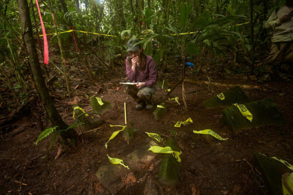 Anna Cohen, a University of Washington anthropology grad student, documents a cache of more than 50 artifacts discovered in the Honduran jungle. Photo Dave Yoder, National Geographic