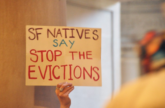 A San Francisco native displays a sign at City Hall for an end to eviction on June 2. Bridgid Skiba