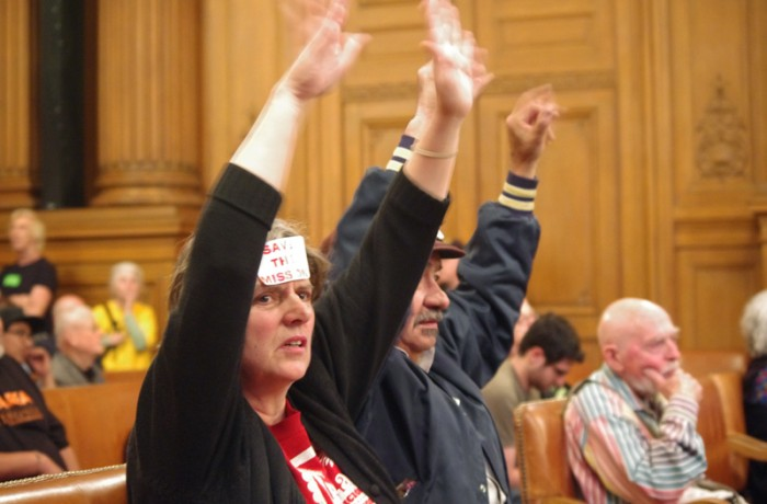 Elizabeth Deyoung (left) applauds fellow supporters of the Mission luxury-housing moratorium by waving her fingers in the air. The nearly 10-hour meeting was paused several time as audience members applauded, cheered and jeered loudly. Photo S. Thollot