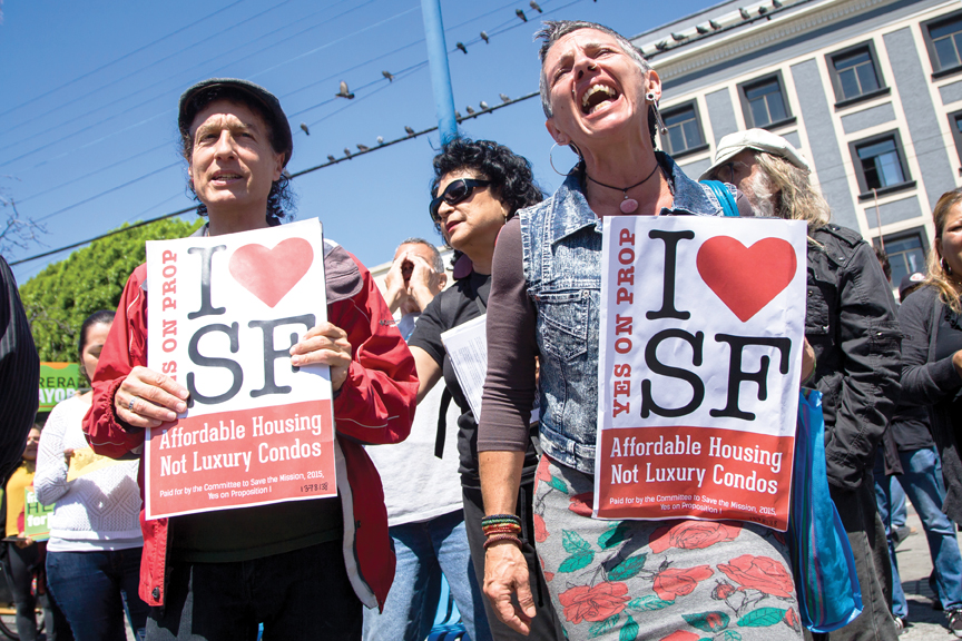 Tommi Avicolli Mecca, counseling director for the Housing Rights Committee of San Francisco, left, and protesters rally at Mission and 16th streets, Aug. 24, 2015. The rally was organized by the Plaza 16 Coalition, an organization formed to challenge the proposed ten-story high-end housing that may displace current long-term residents in the area. Photo Santiago Mejia