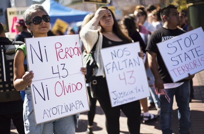 Silvia Castellanos holds a sign that demands no forgiveness, nor oblivion for the 43 missing students of Ayotzinapa, while facing the intersection of 24th and Mission for passerby to see.  Photo Manuel Orbegozo