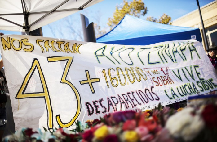 A paper sign shows the number of the Ayotzinapa missing students and of people murdered since the beginning of the Mexican war on drugs in 2006. Photo Manuel Orbegozo