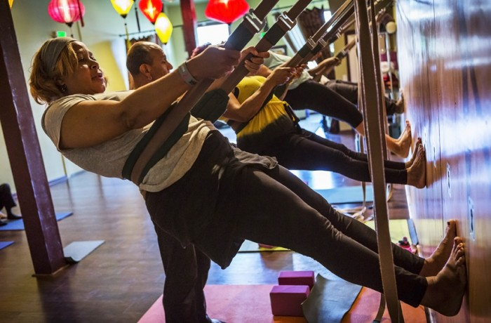 Deborah McNaulty hangs from belts that are hooked to a yoga wall during the seniors' free class on Sept. 19. TriFusion Yoga is the only yoga studio in San Francisco with a yoga wall, according to Luna. Photo Manuel Orbegozo