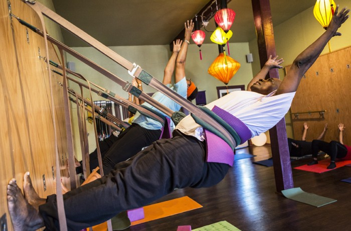 Deborah McNaulty hangs from belts that are hooked to a yoga wall during the seniors' free class on Sept. 19. Trifusion Yoga is the only yoga studio in San Francisco with a yoga wall, according to instructor Armando Luna. Photo Manuel Orbegozo