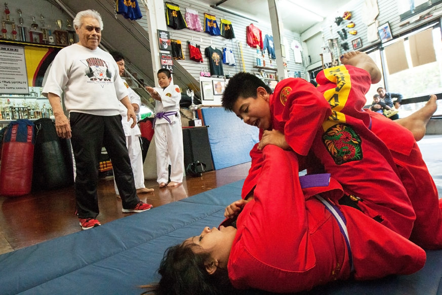 Carlos Navarro, left, referees the practice match between 13-year-old Kevin Balboa, top and Michelle Gonzalez, age 16, at Navarro's Martial Arts Academy, Sept. 4, 2015, in San Francisco, California.