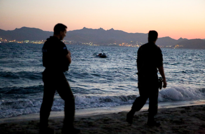 Greek military wait at Lambi Beach in Kos, Greece as a boat carrying four Iraqi migrants makes its way to shore on the morning of July 5, 2015. Migrants and refugees depart from the coast of Bodrum, Turkey, when the sky is dark, arriving on the widespread shore of Kos throughout the night until morning. Authorities wait on the shores of Greece to process names of the migrants and refugees once they land on the island. At times, the coast guard will pick up and rescue migrants and refugees out in the sea if spotted and bring them into the main port of Kos Town. Photo Joel Angel Juárez
