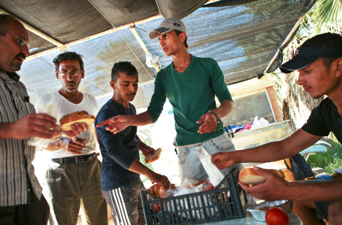 A Palestinian refugee (second to the right) hands out free meals, received from a Greek NGO, to Syrian refugees at the Hotel Captain Elias in Kos, Greece on July 2, 2015. Migrants and refugees are each handed one ticket that is good for one small meal every afternoon by a greek NGO. Migrants and refugees claim that the food is 2-3 days old when they receive it. Many migrants and refugees purchase extra food in the city center because the free meal provided is not sufficient. Photo Joel Angel Juárez