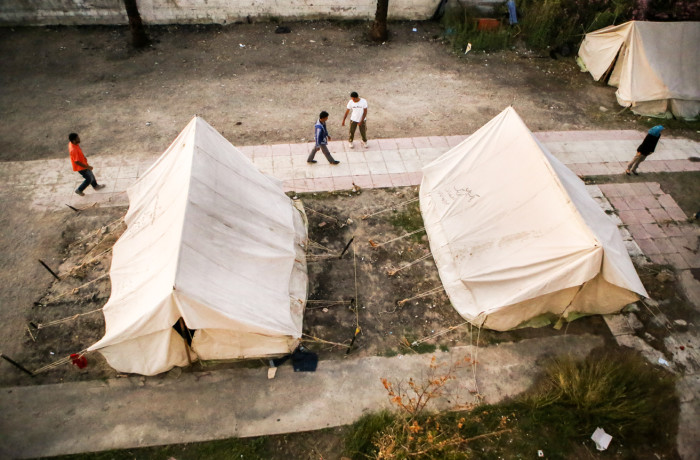 Migrants walk past tents that are used to provide extra shelter at the Hotel Captain Elias in Kos, Greece on July 3, 2015. Doctors Without Borders, an international humanitarian-aid non-governmental organization, set up the tents earlier this year when the greek island of Kos began receiving an influx of migrants and refugees arriving on its shores. Photo Joel Angel Juárez