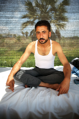 "Hassan, a 28-year-old Syrian Armed Forces defector from Al-Hasakah, poses for a portrait at the Hotel Captain Elias in Kos, Greece on June 29, 2015. ""If anyone found me, I would have been spared no mercy,"" said Hasan through a Syrian refugee who translated from Arabic to English. Hasan defected from the Syrian Armed Forces and claims that he went into hiding for 6 months from the Kurdish Workers Party (PKK) and other rebel groups in Al-Hasakah, the capital city of the Al-Hasakah Governorate located in the far north-eastern corner of Syria. He left his wife and 2-year-old son in Syria after fleeing to the greek island of Kos. ""I was imprisoned for 2 days by the PKK after intelligence and civil service went to my home searching for me ÉI escaped and left Syria,"" Hasan said. Hasan paid $200 USD to illegally cross the Turkish border after 3 failed attempts. He ran for about 3 kilometers after crossing the Turkish border at night until he reached a safe space. He spent the night of his arrival in a Turkish mosque with no one around. The morning after, Hasan took a bus directly to Bodrum, Turkey where he stayed in a hotel with a smuggler for 5 days. Hasan attempted going to Greece everyday, but failed until the fifth day. ""I paid $1,100 to go from Bodrum to Kos,"" said Hasan. ""The smuggler promised me a safety jacket, but I never got one. The smuggler also promised he would bring me my bag with all my things and forgot it. He lied to me,"" said Hassan. Hasan arrived to the island of Kos in a boat carrying about 30 people, 4 of them from Syria and the rest from Afghanistan. ""From Bodrum to Kos, I prayed all the way. I was so afraid,"" said Hasan. Photo Joel Angel Juárez"
