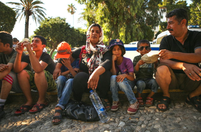 "Salma Abd Alkader (middle) poses for a portrait with her children and husband outside the police station in Kos, Greece as she waits for her name to be called to receive her travel documents on June 29, 2015. The Syrian family paid $2,000 to illegally travel from Bodrum, Turkey to the greek island of Kos in an inflatable dinghy in the darkness of night. Like many migrants and refugees, Abd Alkader fears crossing unknown borders in her journey north into Europe. ""I had fear for this journey. I feared for my children. But now, I feel relaxed because the death stage is finished,"" said Abd Alkader through a Syrian translator who arrived on the island in the same boat. (From left to right) Muhammed Abd Alkader, 14; Anas Abd Alkader, 10; Salma Abd Alkader, 35; Rajmd Abd Alkader, 9; Bilal Abd Alkader, 4; and Khattab Abd Alkader, 50. Photo Joel Angel Juárez"