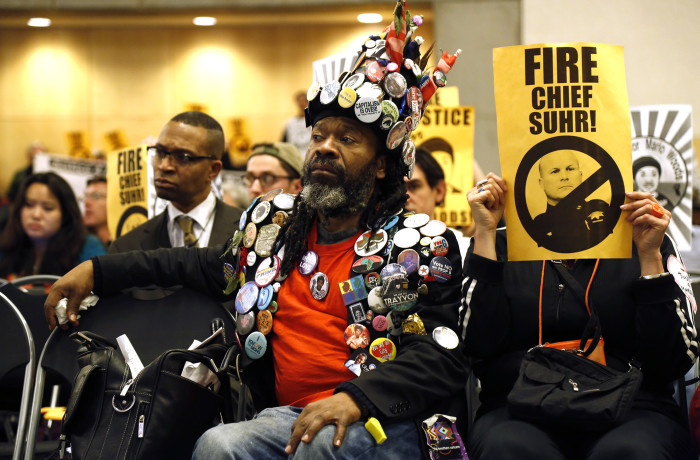 Activist Emond Juicye (middle)  listens to Suzy Loftus, president of the San Francisco Police Commission, at the beginning of the SF Police Commission meeting held at the Salvation Army Kroc Center on Jan. 20 in San Francisco. Photo Emma Marie Chiang