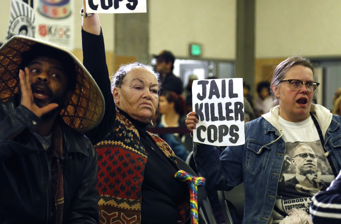 Mesha Irizarry, mother of Idriss Stelley who was shot by three San Francisco police officers in 2001, raises a sign in support of Mario Woods during public comment at the San Francisco Police Commission meeting at the Salvation Army Kroc Center on Jan. 20 in San Francisco. Photo Emma Marie Chiang
