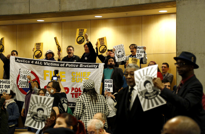 Protesters supporting the Justice 4 Mario Woods Coalition hold signs during public comment at the San Francisco Police Commission meeting at the Salvation Army Kroc Center on Jan. 20 in San Francisco. Photo Emma Marie Chiang