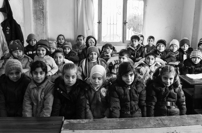 """""""Today's lesson."""" Cramped classrooms and lack of proper heating facilities is common in many schools for Syrian children. Photo Amos Gregory"""