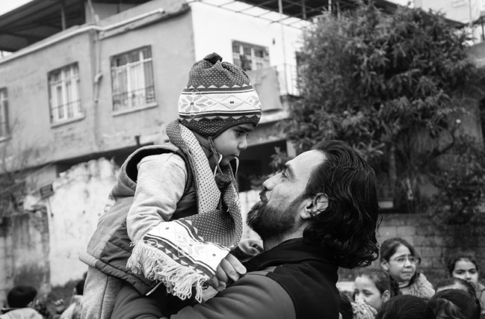 """""""Eyes on the prize."""" Mohammed M., Syrian relief worker holding a student. Photo Amos Gregory"""