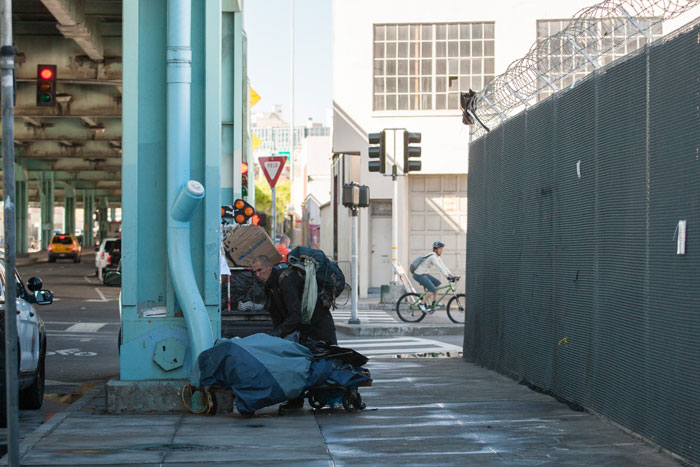 "A homeless man gathers his items as crews from the Department of Public Works ""clean up"" the homeless encampment along Division Street in San Francisco on March 1. City officials declared the encampment a public nuisance. Photo Santiago Mejia."