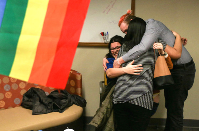 Executive Gay Straight Alliance (GSA) member Chris Hartzler embraces senator Iris Le and student Miranda Samson after learning that Gov. Daugaard vetoed the House Bill 1008. Photo: Ian Lack for The Collegian