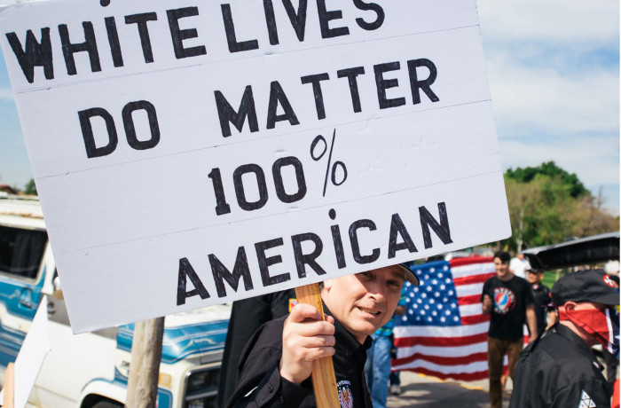 """San Francisco resident and Klansman Charles Edward Donner holds a """"White lives do matter"""" sign during the KKK rally in Anaheim on Feb. 27. A melee soon broke out, resulting in several stabbings and arrests. Donner was arrested for allegedly stabbing three people during the melee, but was released a day later, with police saying he acted in self-defense. Photo courtesy of Eric Hood/OC Weekly"""