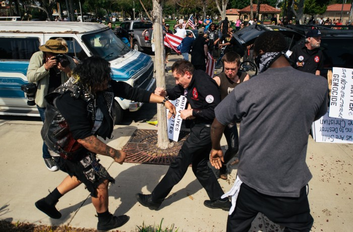 Anti-KKK protester Armando Campos (right) and San Francisco resident and Klansman Charles Edward Donner (center) brawl during the melee that broke out at the KKK rally in Anaheim on Feb. 27. Photo courtesy of Eric Hood/OC Weekly
