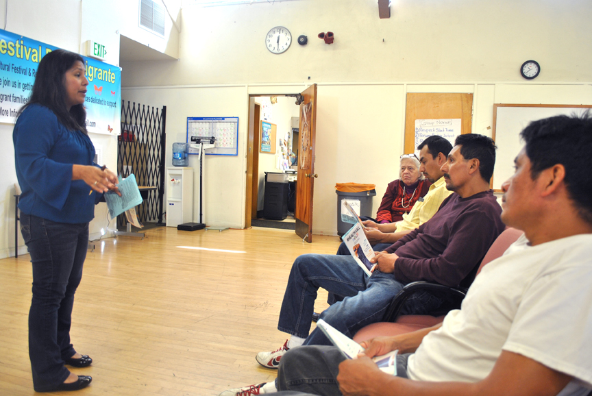 Volunteer Laura Lopez explains SB-4 to parents, the new bill that will expand Medi-Cal coverage to undocumented immigrant children under the age of 19, in Hayward on March 26.  Photo Alejandro Galicia Díaz