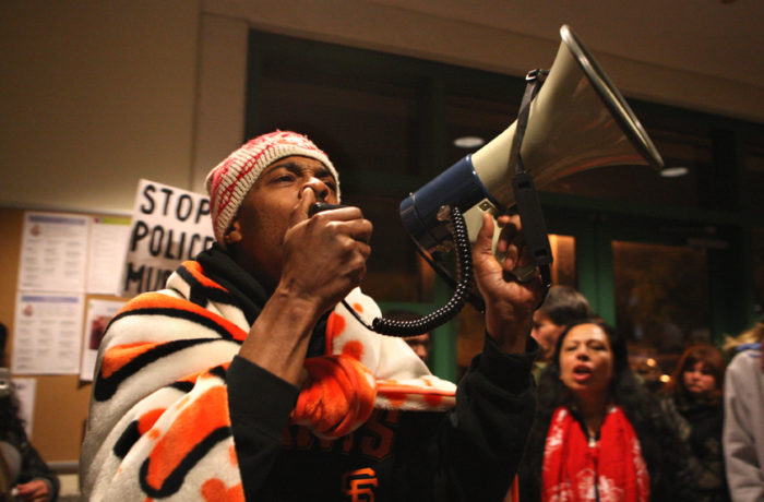 Bay area rapper Sellassie speaks into a into a megaphone after officers at the Mission Police Station refused to open the bathrooms in the building for at least two pregnant women and a child during day five of a hunger strike on April 25. Photo Joel Angel Juárez