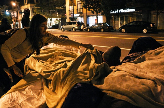 Eva Kane places a blanket on a protestor sleeping in their chair minutes past midnight in front of the Mission Police Station marking the end of day five of a hunger strike. Photo Joel Angel Juárez