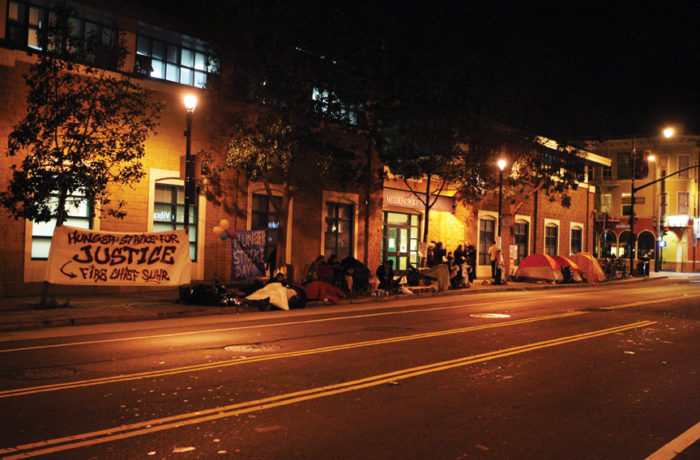 Protestors rest on the sidewalk minutes past midnight in front of the Mission Police Station marking the end of day five of a hunger strike demanding the resignation of SFPD Police Chief Greg Suhr. Photo Joel Angel Juárez