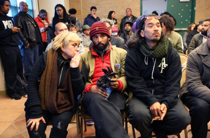 """Maria Cristina Gutierrez (left), Edwin Lindo (middle) and Ilyich """"Equipto"""" Sato (right) sit at the start of a weekly community meeting of day six of a hunger strike demanding the resignation of SFPD Police Chief Greg Suhr on April 26, 2016.  Ilyich Sato, a Bay Area rapper known as Equipto, is leading the group of protestors in the hunger strike targeting police brutality and city gentrification. Sato said the group will only consume liquids and will stay put in front of the Mission Police Station located on Valencia and 17th streets until either Lee or Suhr resign even if that means risking arrest. Photo Joel Angel Juárez"""