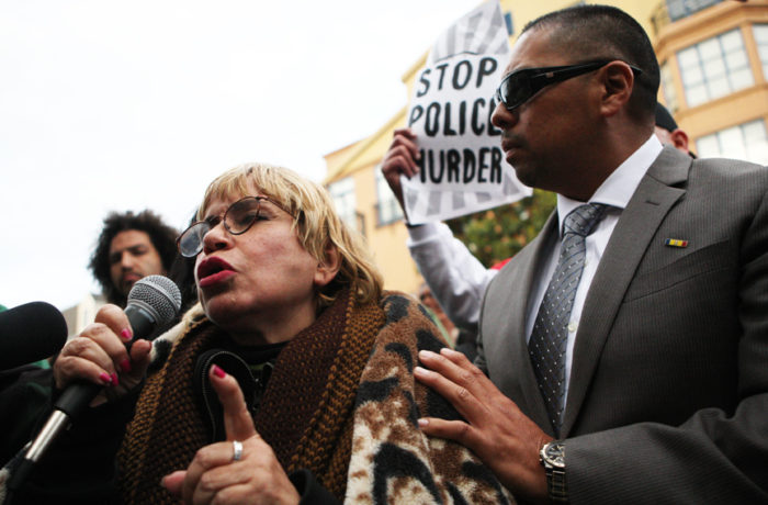 Maria Cristina Gutierrez (left) speaks as Benjamin Bac Sierra (right) stands by her side as protestors rally outside the Mission Police Station after SFPD Captain Daniel Perea cancelled a monthly community meeting during day six of a hunger strike. Photo Joel Angel Juárez