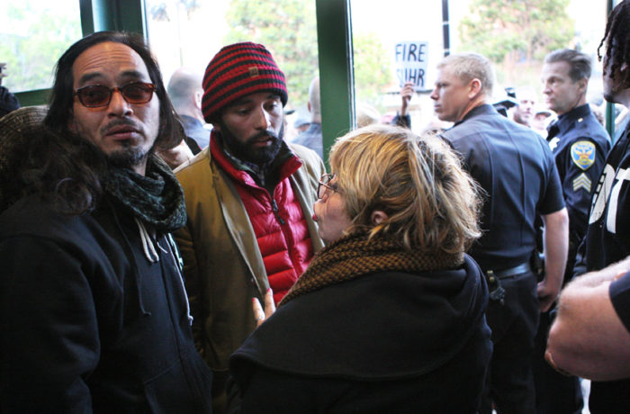 """Ilyich """"Equipto"""" Sato (left), Edwin Lindo (middle) and Maria Cristina Gutierrez (right) talk to each other inside the Mission Police Station after SFPD Captain Daniel Perea cancelled a monthly community meeting during day six of a hunger strike. Photo Joel Angel Juárez"""