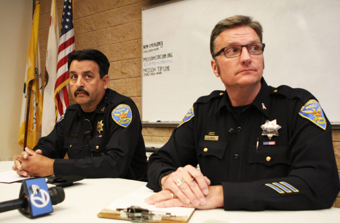 SFPD Captain Daniel Perea (left) and Officer Steven Keith (right) listen to protestors demanding that the monthly community meeting be held outside to accommodate the overflow of people waiting outside. Photo Joel Angel Juárez
