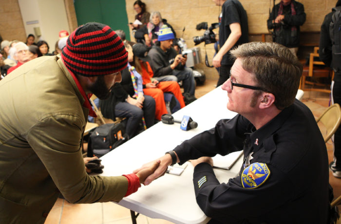 Hunger striker Edwin Lindo (left) shakes Officer Steven Keith's (right) hand at the start of a monthly community meeting held at the Mission police Station during day six of a hunger strike. Photo Joel Angel Juárez