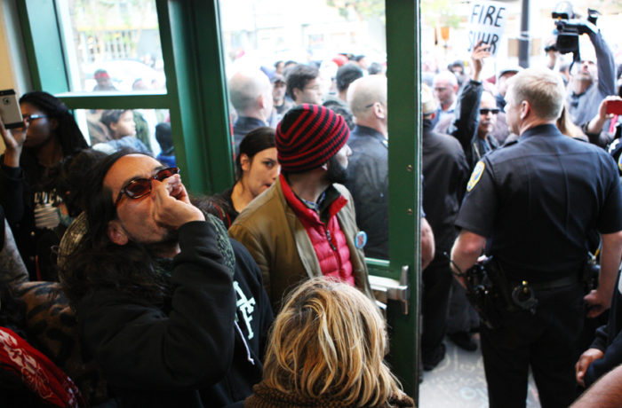 """Ilyich """"Equipto"""" Sato (left) rallies inside the Mission Police Station after SFPD Captain Daniel Perea cancelled a monthly community meeting during day six of a hunger strike. Photo Joel Angel Juárez"""