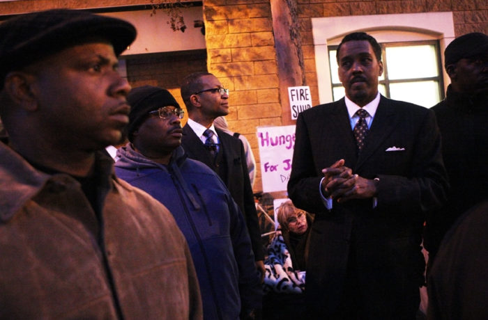 Minister Christopher Muhammad (right) of the Nation of Islam stands in front of the Mission Police Station after protestors occupied the intersection of Valencia and 17th streets as SFPD Captain Daniel Perea cancelled a monthly community meeting during day six of a hunger strike. Photo Joel Angel Juárez