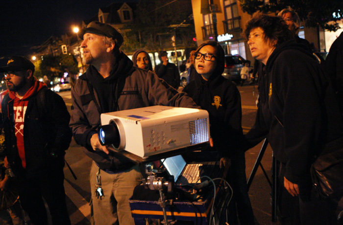 Protestors set up a projector with video of the hunger strike movement against SFPD in front of the Mission Police Station after occupying the intersection of Valencia and 17th streets after SFPD Captain Daniel Perea cancelled a monthly community meeting during day six of a hunger strike. Photo Joel Angel Juárez