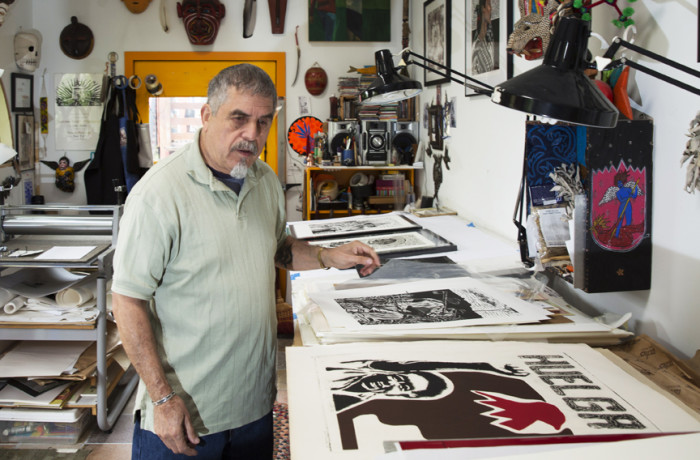 """Juan Fuentes at his home studio, next to his poster """"Huelga."""" Originally done as a collagraph, it was his first piece to depict the struggle of farmworkers. Photo Drago Rentería"""