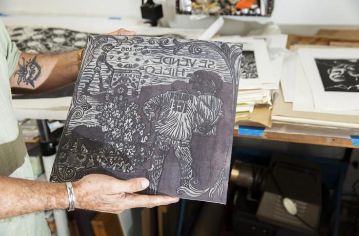 Juan Fuentes holds the carved block of his linocut piece Se Vende, 2012. Photo Drago Rentería