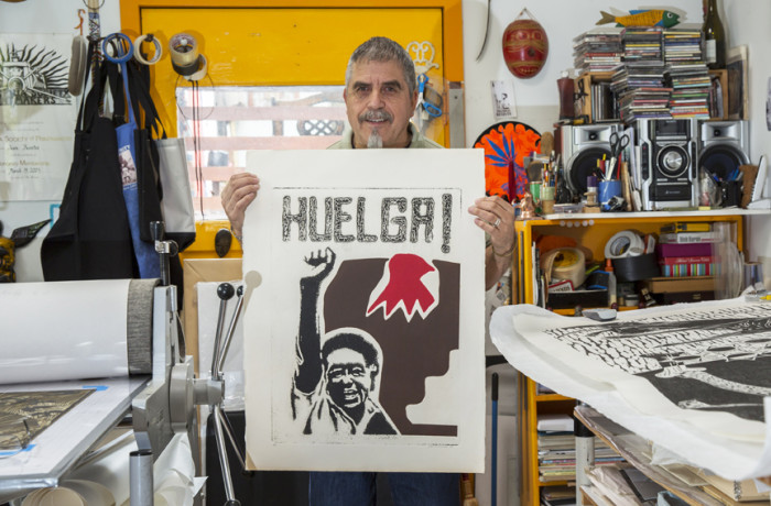 """Juan Fuentes at his home studio, holding his poster """"Huelga."""" It was his first piece to depict the struggle of farmworkers. Photo Drago Rentería"""