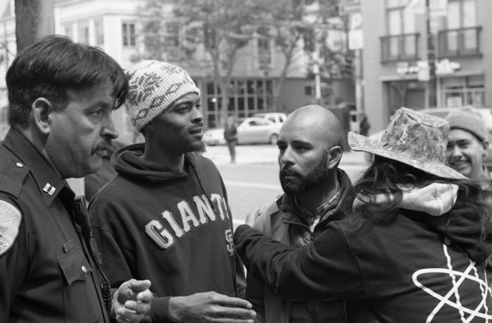 """SFPD Captain Daniel Perea (left) during a tense meeting with hunger strikers Sellassie Blackwell, Edwin Lindo and Ilyich """"EQUIPTO"""" Sato and Edwin Lindo during day six of the strike demanding the resignation of SFPD Police Chief Greg Suhr. Photo John Morrison"""