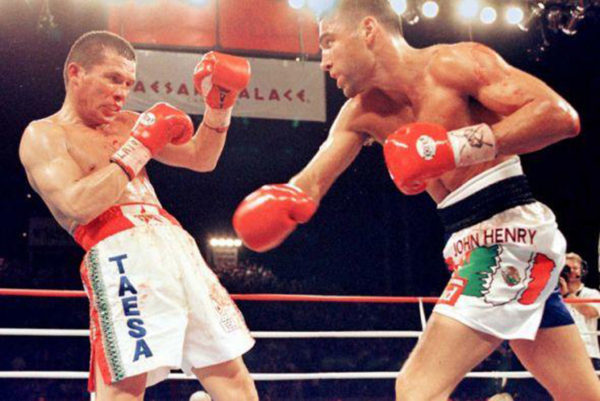 Mexican American boxer Oscar De La Hoya (right) defeats Mexican icon Julio Cesar Chavez on June 7, 1996. The victory catapulted De La Hoya's boxing career, but he became villainized by many Mexican boxing fans. AFP PHOTO/John Gurzinksi