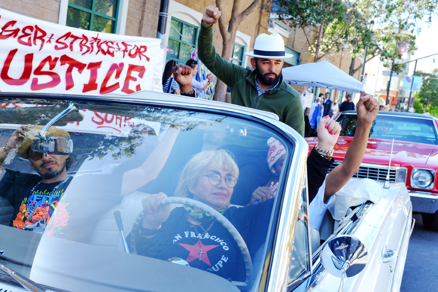 """The """"Frisco Five,"""" a group of people on hunger strike outside the Mission Police Station, are cheered on by lowrider drivers and supporters, Sunday, May 1, 2016 in San Francisco, Calif. Maria Cristina Gutierrez, age 66, is seen at the wheel with her 42-year-old son Ilych Sato to her right. Edwin Lindo, age 29, is seen sitting on top of the car and to his left, Sellassie Blackwell, 39, and 42-year-old Ike Pinkston (to Lindo's right). Photo by Santiago Mejia."""