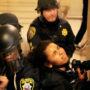 La fotógrafa de El Tecolote, Gabriella Angotti-Jones es detenida por dos ayudantes del alguacil mientras se encontraba cubriendo la protesta del 6 de mayo. Foto Noé Serfaty