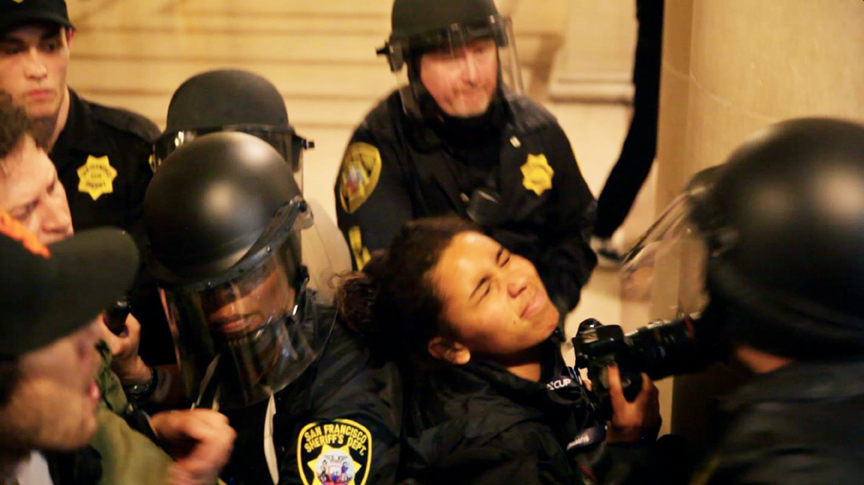 El Tecolote photographer Gabriella Angotti-Jones is grabbed by two Sheriff's Deputies while covering a protest at City Hall on May 6. Photo Noé Serfaty